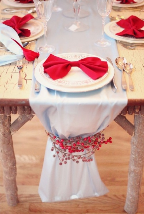 a natural Christmas tablescape with a grey table runner decorated with red berries, plates with red bows and silver cutlery