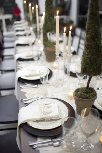 a natural Christmas table setting with black chargers, mini moss trees in pots, macrame tree napkin rings, tall candles and newspaper runners