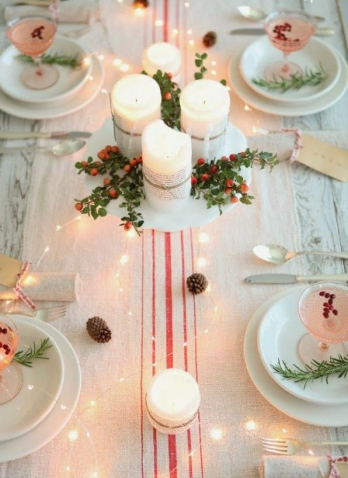 a neutral Christmas tablescape with a striped table runner, white porcelain and cranberry cocktails, pinecones, lights and a centerpiece of candles, berries and greenery