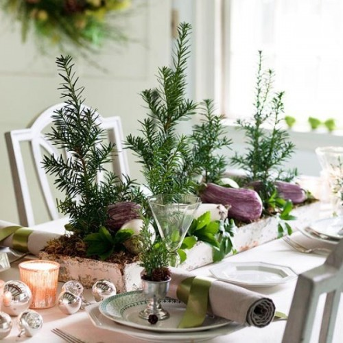 a natural Christmas tablescape with Christmas trees, a box centerpiece with veggies and greenery, metallic ornaments and candles, pinecones and evergreens in cups