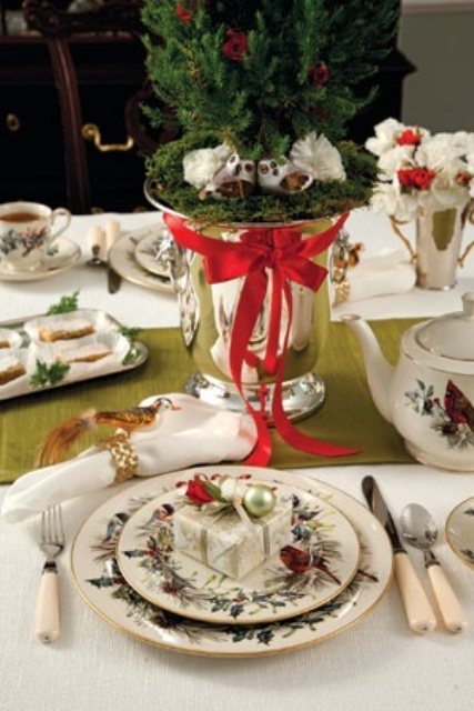 a red, green and white Christmas tablescape with a green runner, a Christmas tree in a vase, white and red blooms and minni ornaments