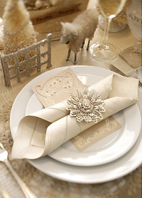 a white and glitter Christmas table with mini white trees, sheep figurines, a glitter tablecloth, a napkin with a sequin napkin ring