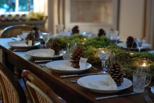 a natural Christmas table with moss and candles, pinecones, white porcelain and elegant glasses