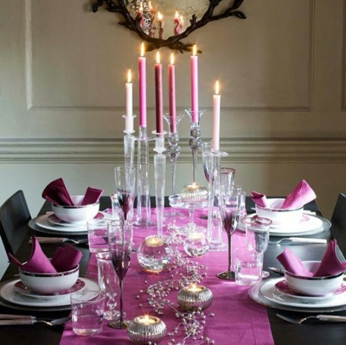 a bright Christmas tablescape with fuchsia napkins and a runner, tall and thin candles, mercury glass candleholders and printed floral porcelain