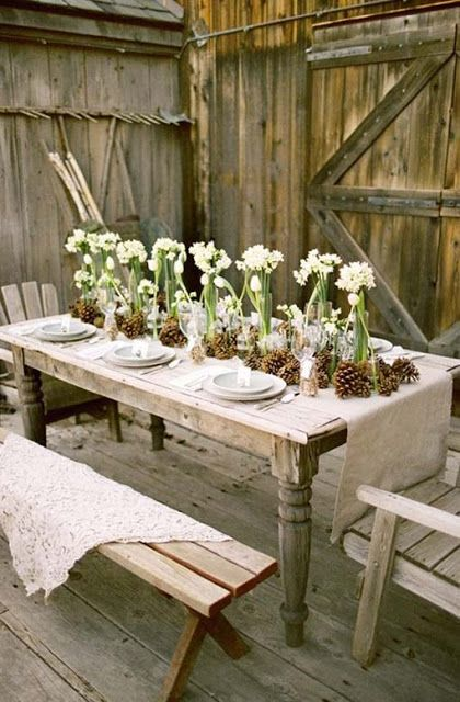 a cozy Christmas tablescape with a burlap table runner, pinecones and neutral blooms and macrame covers on the benches