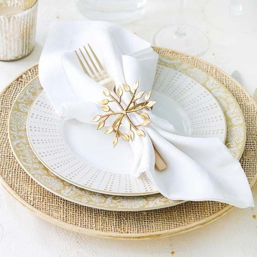 a gold and white Christmas tablescape with gold chargers and snowflake napkin rings, mercury glass candleholders and white napkins