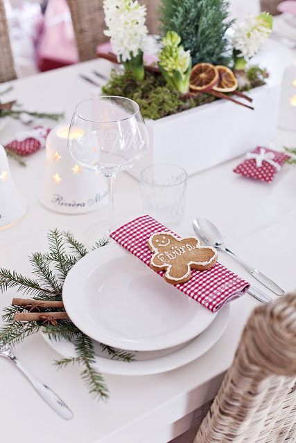 a homey Christmas wedding table with candles, plaid napkins, evergreens, cinnamon bark, gingerbread cookies and bloom centerpieces
