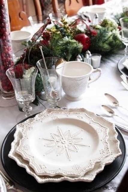 a refined Christmas wedding table with black chargers and white snowflake plates, evergreens and apples, candles and cranberries in vases