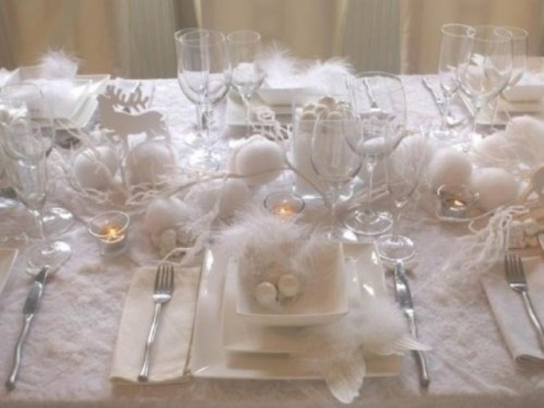 a pure white Christmas table with felt snowballs, feathers, ornaments, deer figurines and all-white everything