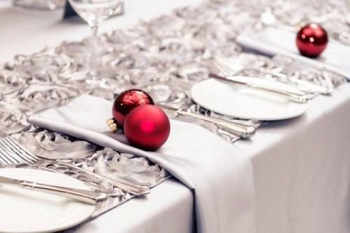 a grey and white Christmas tablescape spruced up with red ornaments and silver cutlery