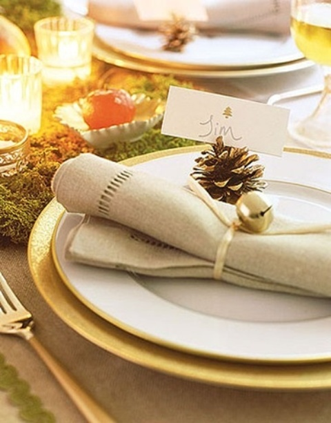 a chic Christmas place setting with moss, candles, apples, a gold charger, a napkin with a pinecone and a bell