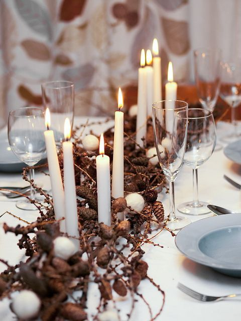 a natural Christmas tablescape with blue plates, dried branches and pinecones, candles and felt snowballs