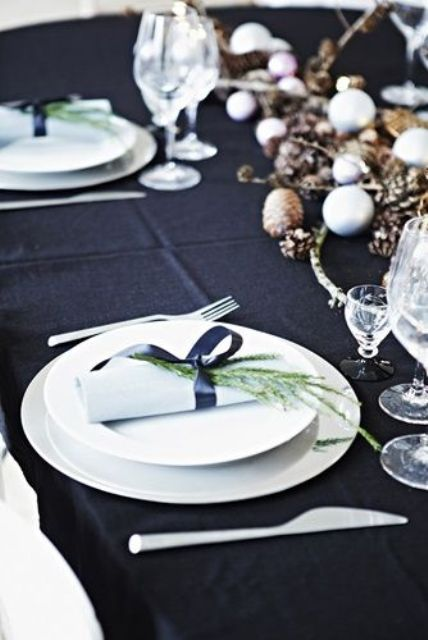 a dark natural tablescape with a black tablecloth, dried branches and acorns, black ribbons and evergreens