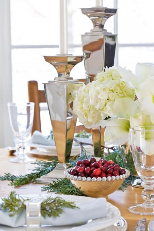 a natural meets glam Christmas table setting with large shiny vases, white blooms, evergreens, cranberries and shiny napkin rings
