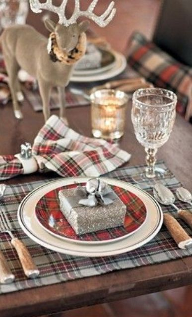 a cozy Christmas table setting with plaid placemats and napkins, a shiny glitter deer, a glitter favor box with a bell on top