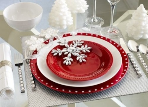 a red and white Christmas tablescape with silver placemats, red plates, snowflakes and faux snow