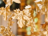 garlands of gold faux leaves hanging down compose a unique and beautiful fall wedding backdrop, you can DIY it and save the budget
