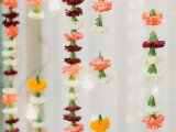 vertical garlands of bright carnations hanging down is a pretty and easy wedding decor idea, and you can make a backdrop of them