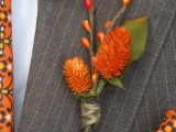 a bold fall wedding boutonniere with faux berries and bright orange blooms plus a leaf for a rustic fall wedding