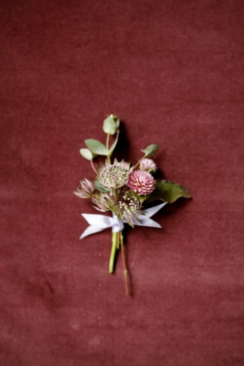 a delicate fall wedding boutonniere with leaves and dried pink blooms will fit many weddings with a slight decadent feel
