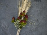 a lovely fall wedding boutonniere with spikes, berries and greenery and twine wrap for a rustic fall wedding look