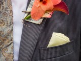 a bright wedding boutonniere with an orange bloom, green and bright leaves and branches for a fall groom