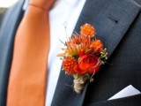 a bold dried bloom boutonniere in orange and deep red matching a bold orange tie to accessorize a fall groom's look