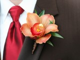 a bold rust-colored wedding boutonniere with greenery and a bright red tie for a chic and bold groom's look