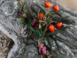 a boho fall wedding boutonniere with berries, nuts, greenery and blooms and grasses is amazing