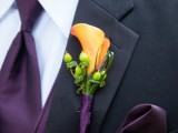 a bright wedding boutonniere with an orange calla and green berries plus grasses is a stylish and bold idea for a fall groom