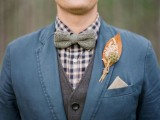 a bright fall wedding boutonniere with a bold and large leaf, some blooms and greenery for a vintage-inspired rustic wedding