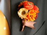 a bright wedding boutonniere with red, yellow and orange blooms and brown ribbon is chic and cool