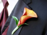 an orange calla lily with leaves is a timeless and cool wedding boutonniere for a bold fall groom's look