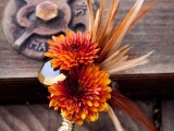 a bright wedding boutonniere with orange blooms, feathers and a bold tan crystal is a chic and bold accessory to rock