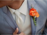 a brigth orange bloom wedding boutonniere with berries is timeless classics for a fall wedding