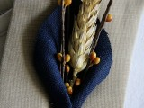 a rustic fall wedding boutonniere with navy fabric, faux berries, a spike for a rustic fall wedding