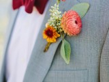 a bright fall wedding boutonniere with red and yellow blooms and some leaves is a stylish solution for a fall wedding