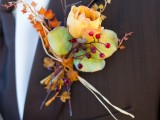 a bold fall wedding boutonniere with fall leaves, a bright bloom and berries is a stylish and cool idea for a bright fall wedding