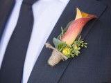a refined wedding boutonniere with an orange calla lily, yellow blooms and berries and twine wrap for an elegant groom's look