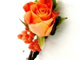 a bright fall wedding boutonniere with berries and an orange rose plus leaves is a stylish idea