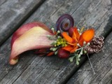 a bright wedding boutonniere with a burgundy calla lily and bright blooms plus greenery is wow