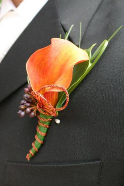 a bright fall wedding boutonniere with a single orange calla and berries plus some leaves is a cool idea for a modern groom