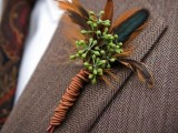 a boho fall wedding boutonniere with bright feathers, berries and bright twine is a lovely and bold accessory for a fall wedding