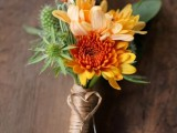 a bright fall wedding boutonniere with orange, yellow and lilac blooms and thistles is a bright idea for a rustic fall wedding