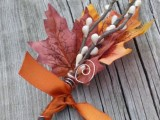 a bold fall wedding boutonniere of bright leaves, faux berries, rust ribbon and copper wire