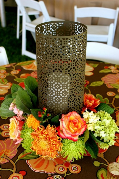 an elegant fall wedding centepiece of a laser cut candleholder and greenery and bright blooms around it