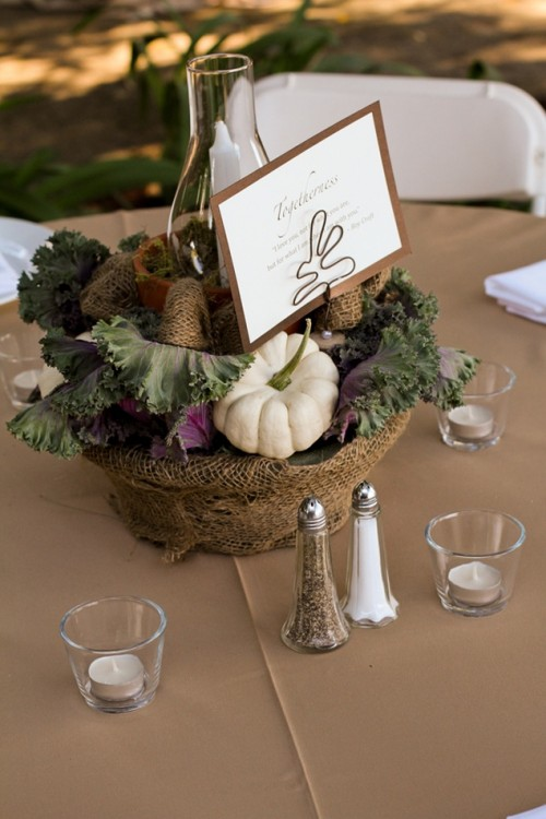 a rustic fall centerpiece of a bowl wrapped with burlap, soem veggies and a candle plus a large card on top