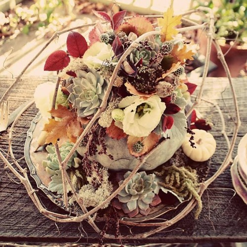 a super creative and textural wedding centerpiece of veggies, succulents, fall leaves and blooms plus some twigs on top