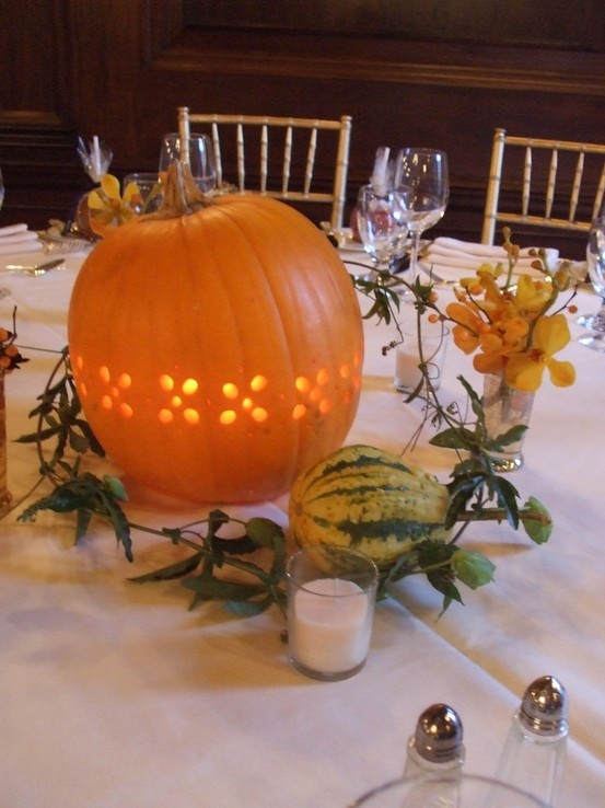 a cutout pumpkin candleholder, some blooms, greenery, a zucchini, candles for a creative fall wedding centerpiece