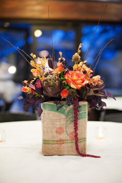 a bright fall wedding centerpiece in a vase wrapped with burlap, bright and dark blooms and artichokes